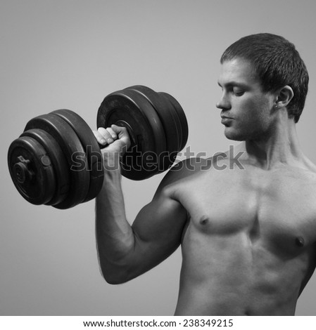 Handsome muscular male model with dumbbell. Black and white. - stock photo