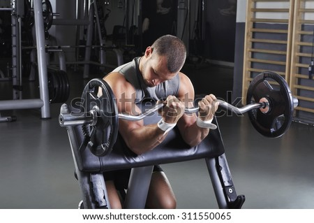 Handsome Muscular Male Model With Perfect Body Doing Biceps Exercise - stock photo
