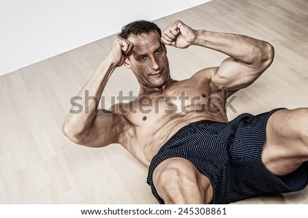 Handsome muscular man doing fitness exercise - stock photo