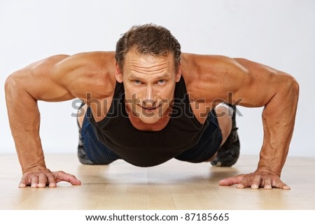 Handsome muscular man doing push-up. - stock photo