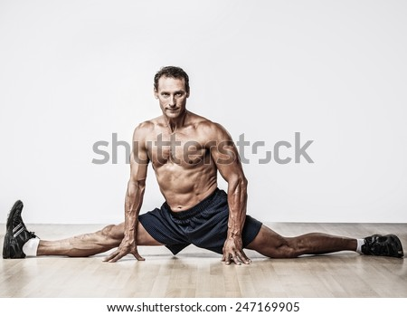 Handsome muscular man doing splits - stock photo