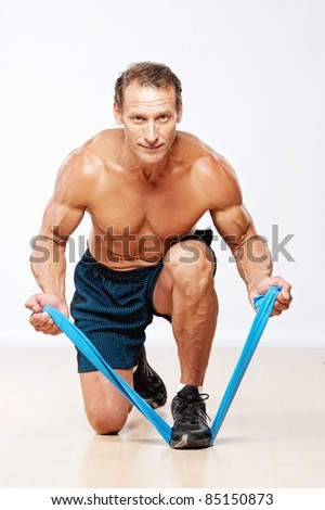 Handsome muscular man doing stretching exercise. - stock photo