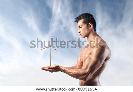 Handsome muscular man holding a windmill in his hands - stock photo