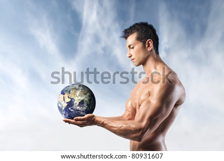 Handsome muscular man holding the Earth in his hands - stock photo