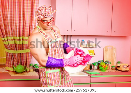 Handsome muscular man in an apron cooking in the pink kitchen. Love concept. Valentine's day.  - stock photo