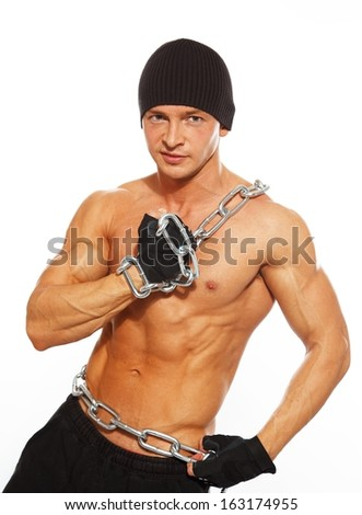 Handsome muscular man in beanie hat with chain - stock photo