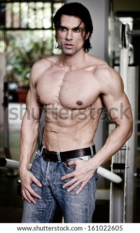 Handsome muscular man in jeans shirtless looking away, showing ripped torso - stock photo