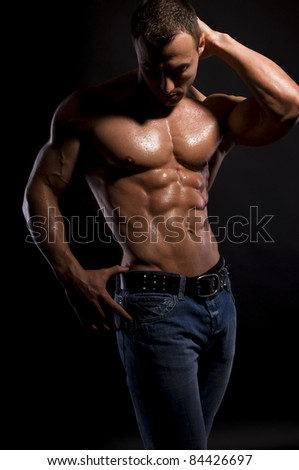Handsome, muscular man in jeans  with water-drops - stock photo