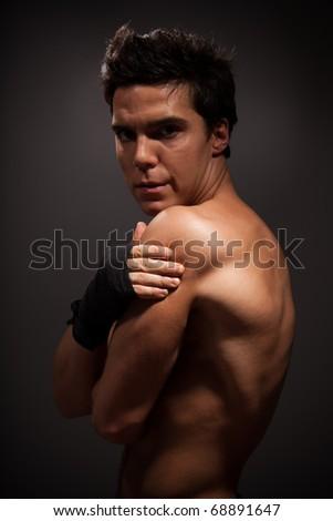 Handsome muscular man looking at camera behind his shoulder - stock photo
