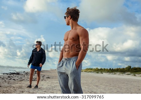 Handsome muscular man on a beach over blue sky with clouds. - stock photo