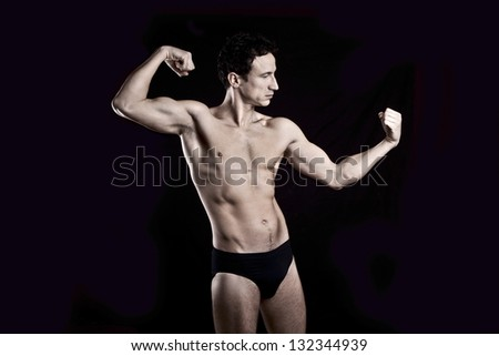 Handsome muscular man on black background - stock photo