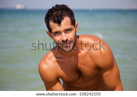 Handsome muscular man on the beach. - stock photo