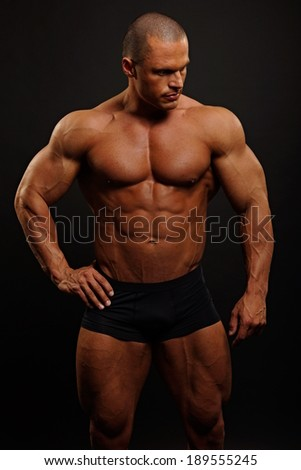 Handsome muscular man poses on dark background