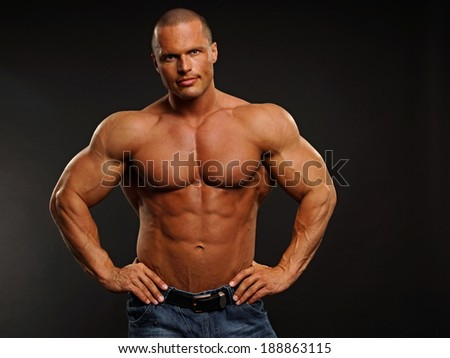 Handsome muscular man poses on gray background