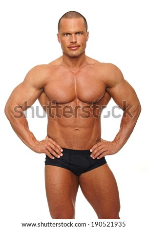 Handsome muscular man poses on white background