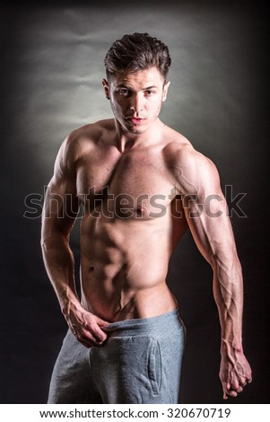 Handsome muscular man posing against a dark background - stock photo