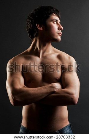 handsome muscular man posing against dark background - stock photo