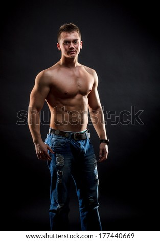 Handsome muscular man posing in jeans
