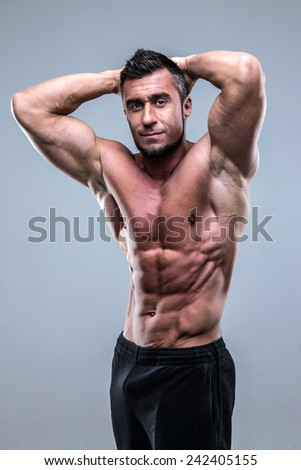 Handsome muscular man posing over gray background
