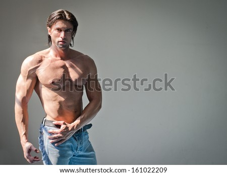 Handsome muscular man shirtless wearing jeans on grey background - stock photo