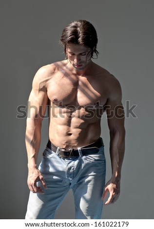 Handsome muscular man shirtless wearing jeans on grey background looking down - stock photo