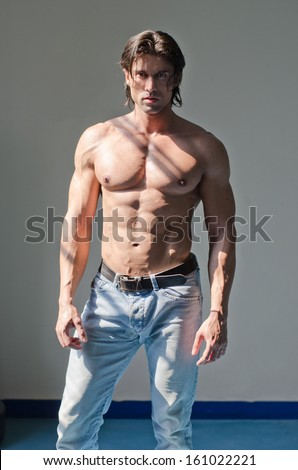 Handsome muscular man shirtless wearing jeans on grey background looking in camera - stock photo