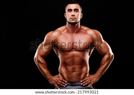 Handsome muscular man shirtless wearing white pants over black background - stock photo