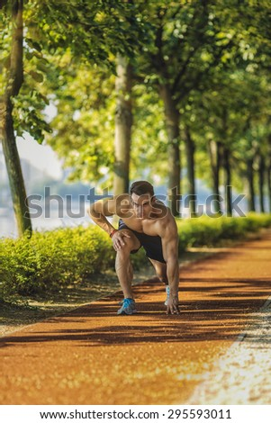 Handsome muscular man training in the city park at summer - stock photo