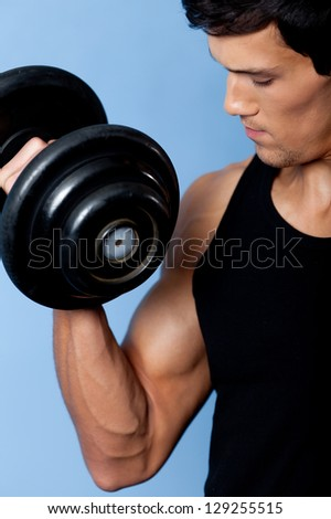 Handsome muscular man uses his dumbbell to exercise flexing bicep muscle, close up - stock photo