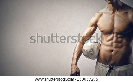 handsome muscular man with ball on gray background - stock photo