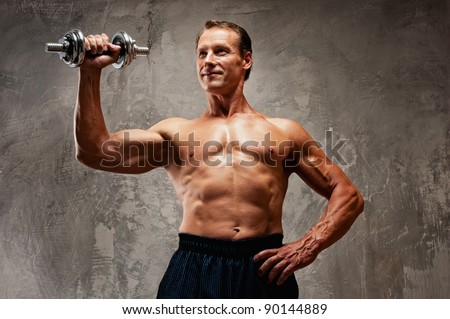 Handsome muscular man with dumbbell