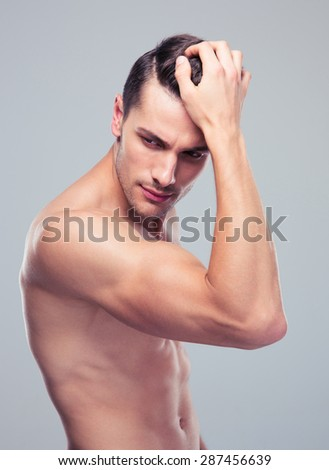 Handsome muscular man with naked torso posing over gray background - stock photo