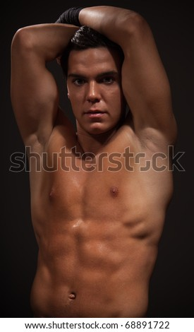 Handsome muscular man with strong arms on dark background - stock photo