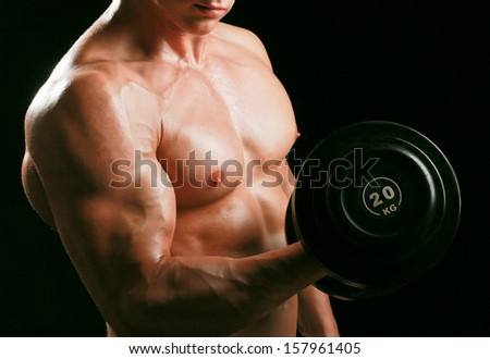 Handsome muscular man working out with dumbbells on black background - stock photo