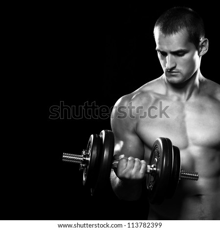 Handsome muscular man working out with dumbbells over black background - stock photo