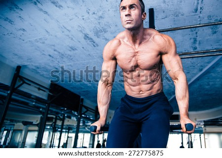 Handsome muscular man workout on bars in gym - stock photo