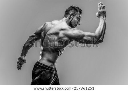 Handsome muscular mna posing over gray background. HDR monochrome - stock photo