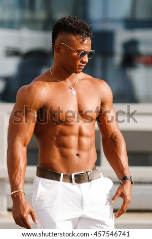 Handsome muscular Shirtless Hunk man outdoor in the city, without a shirt, showing his muscles. Black guy with a naked torso on a background of urban houses. - stock photo
