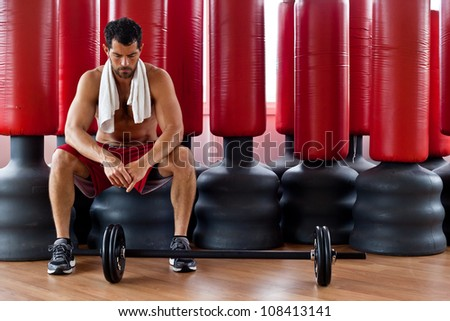 Handsome muscular sports man with a towel on his shoulders looking tense in front of red punching bags. Fighter. - stock photo
