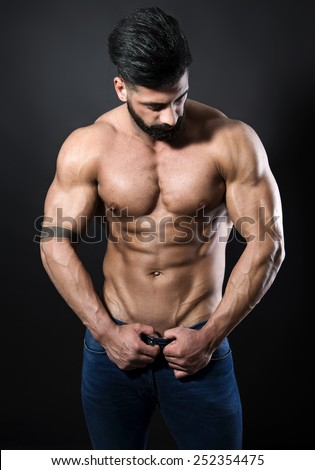 handsome muscular young bodybuilder showing his muscles and abs while posing shirtless - stock photo