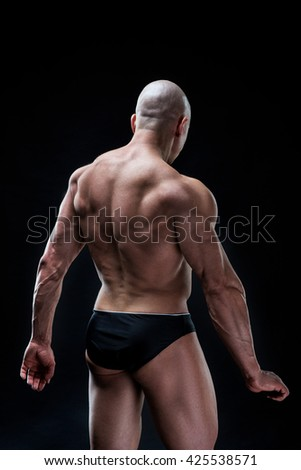 handsome muscular young bodybuilder showing his muscles and abs while posing shirtless.  Isolated on black background - stock photo