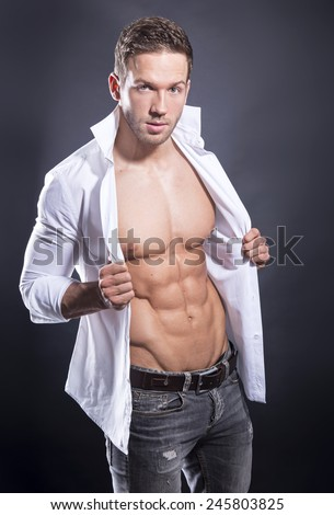 handsome muscular young bodybuilder showing off his perfect abs and muscles while posing in open shirt - stock photo