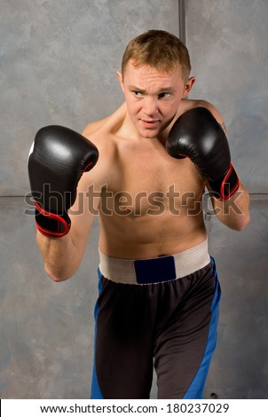 Handsome muscular young boxer standing with his gloved fists raised and a look of determined concentration on his face - stock photo