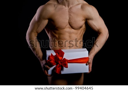 handsome muscular young man holding a present. Christmas. - stock photo