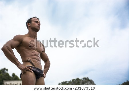 Handsome muscular young man in bathing suit shot from below, large copyspace on the sky - stock photo