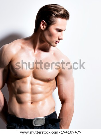 Handsome muscular young man looking sideways posing at studio on a white background with contrast shadows. - stock photo