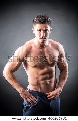 Handsome, muscular young man on a black background - stock photo