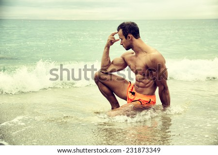Handsome muscular young man on the beach sitting in the sea in profile pose - stock photo