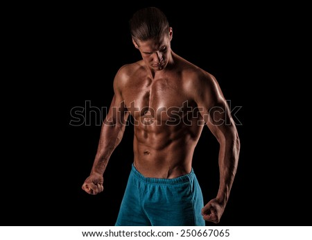 handsome muscular young man posing in front of the camera in the studio