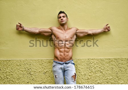 Handsome, muscular young man shirtless with arms spread open, leaning against yellow wall - stock photo